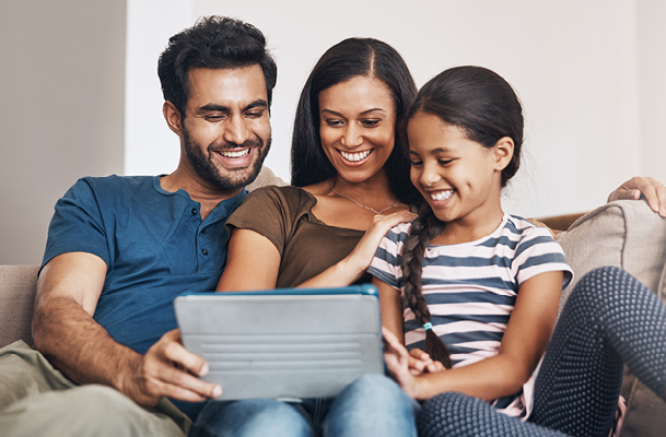 Family of three looking at a tablet on a couch