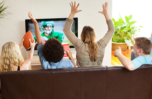 Four people watching football cheering on a couch
