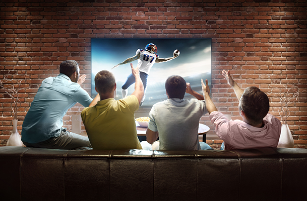 Four friends watching football on a couch cheering