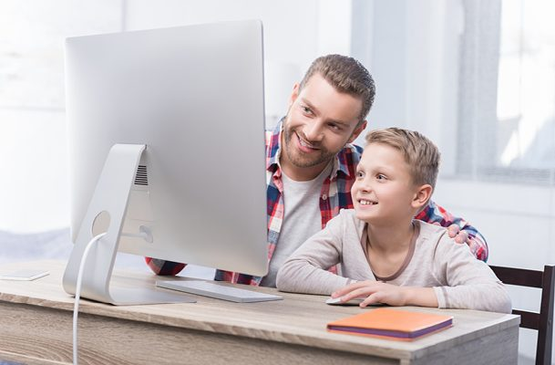Father and son working on a desktop computer