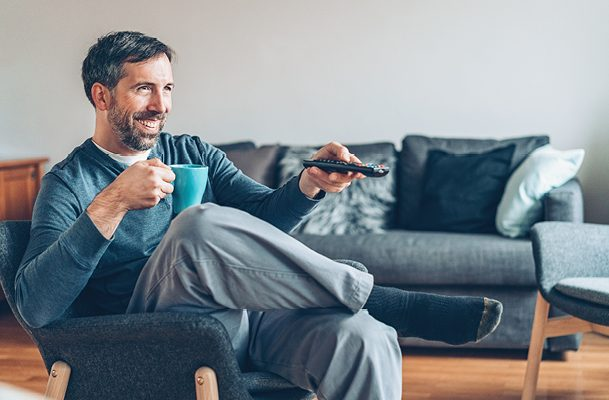 Man sitting in a chair smiling, drinking coffee and watching TV