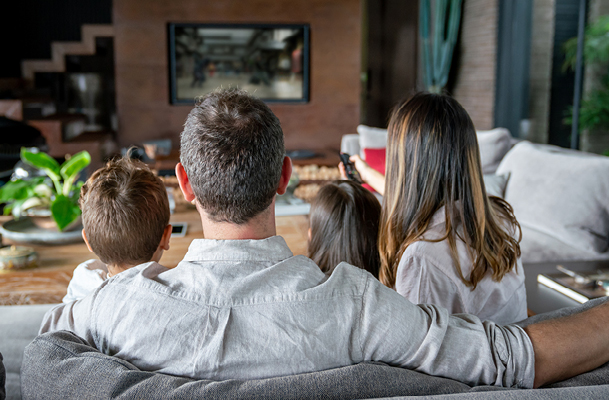Family of four sitting on a couch watching TV