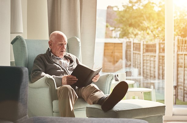 Elderly man sitting in a chair reading a book
