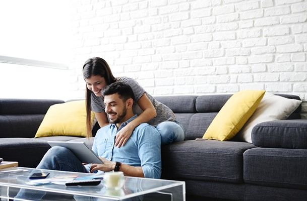 Couple relaxing on a couch looking at a laptop