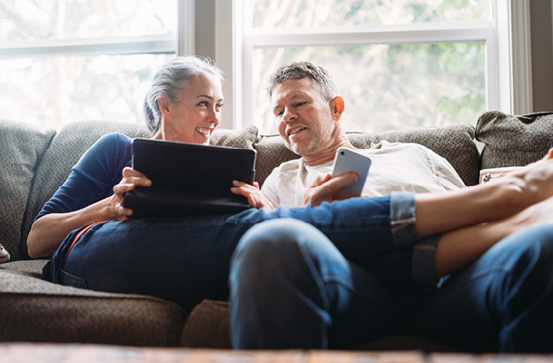 Couple sitting on couch on a tablet and cell phone