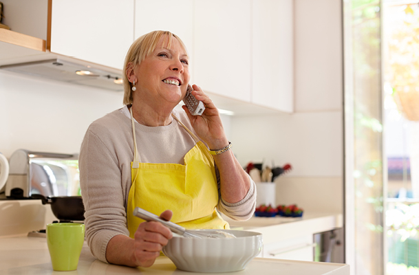 Elderly woman cooking while on a landline phone