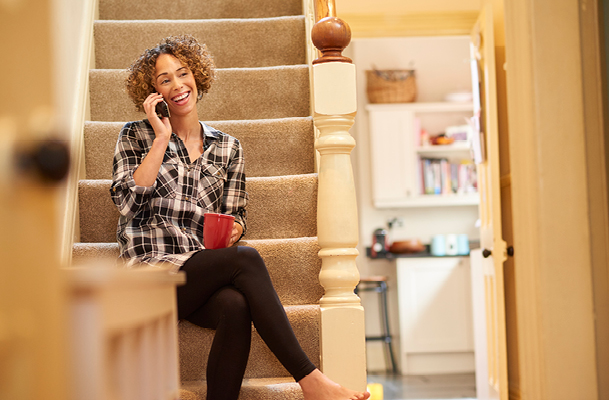 Woman sitting on the stairs on a landline phone smiling