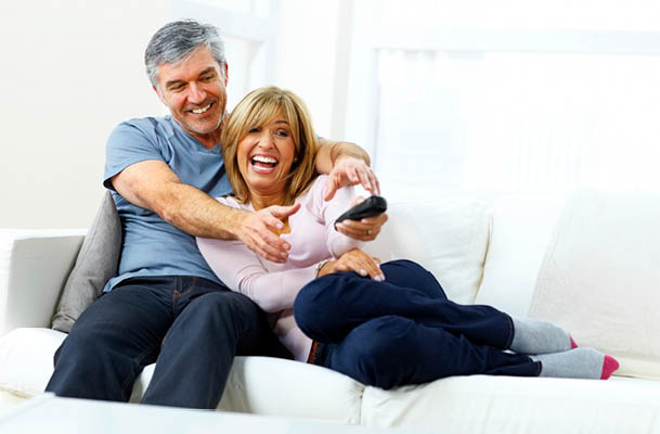 Couple laughing and watching TV together